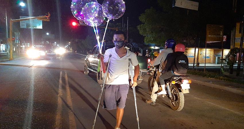 Pese a su discapacidad, Sergio David Moncada se arriesga en la carretera a vender globos. Foto: Famnuel Úbeda/Radio ABC Stereo